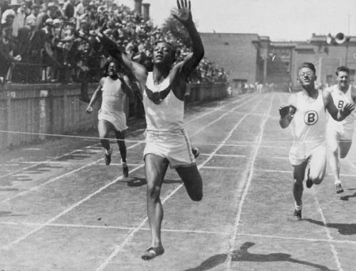 11th June 1932:  Cleveland high school student and future Olympic champion Jesse Owens (1913 - 1980) holds his hands in the air while crossing a finish line to break the world 100-meter record.  (Photo by New York Times Co./Getty Images)
